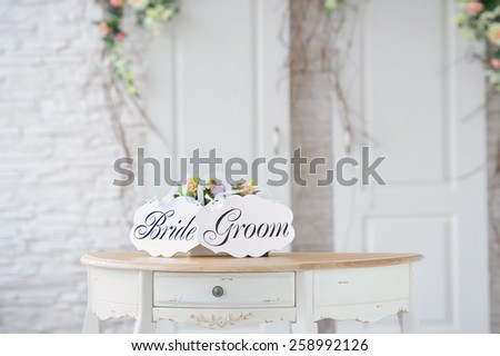 Vintage wedding decoration with flowers and bride groom boards  - stock photo