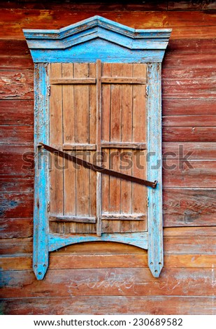 Vintage window of wooden hut in traditional Russian style in Astrakhan, Russia. Closeup detail of the exterior of wooden house. Window with closed shutters painted in brown and bright  blue color - stock photo