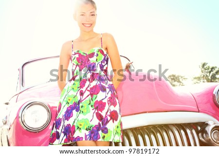Vintage woman and car. Old retro style car and beautiful young happy smiling woman on road trip. Pretty mixed race Caucasian / Asian Chinese female lifestyle model. Photo from Havana, Cuba. - stock photo