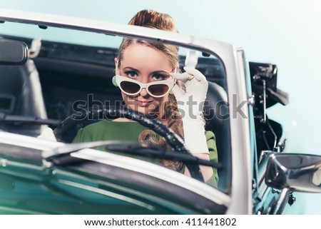 Vintage 1960 woman in convertible car looking over sunglasses. - stock photo