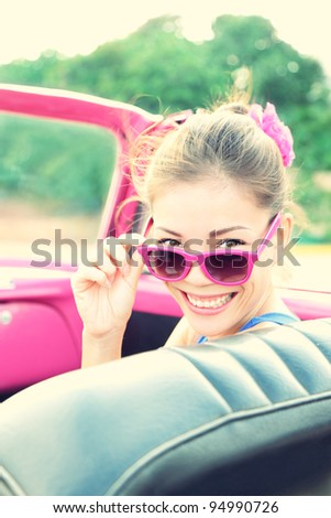 Vintage woman in pink retro car. Retro vintage processed photo of girl on road trip driving in vintage cabriolet car during summer holidays.
