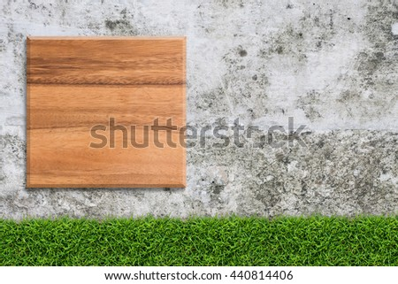Vintage wood board on concrete wall texture background with green grass. - stock photo