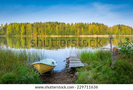 Vintage wood boat and pier at calm beautiful northern lake - stock photo