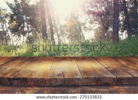 vintage wooden board table in front of dreamy and abstract forest landscape with lens flare.  - stock photo