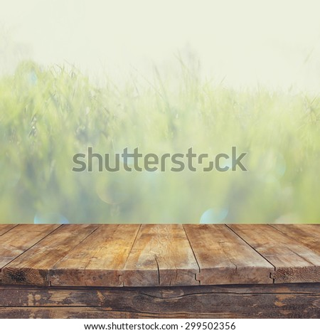vintage wooden board table in front of dreamy and abstract landscape with lens flare.  - stock photo
