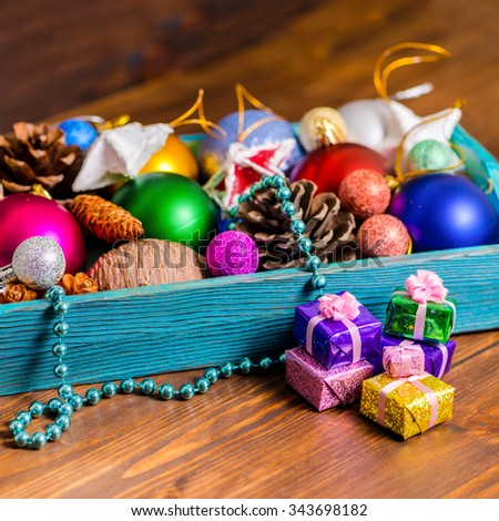 vintage wooden box with Christmas decoration, tinsel,  pinecones, stars, balls and gifts on wooden background, closeup - stock photo