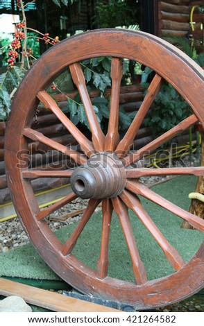 Vintage wooden cart wheel on green.