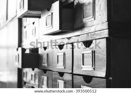 Vintage wooden catalog with some drawers opened. One of the drawers has label with the word Data on it. Black and white. - stock photo