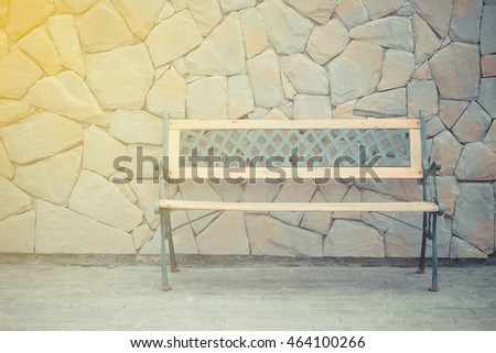 Vintage wooden chair with stone wall background