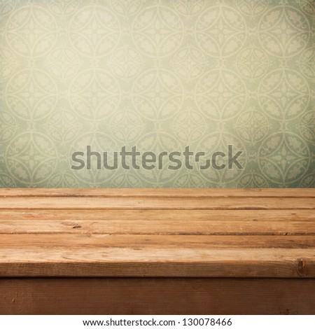 Vintage wooden deck table over grunge wallpaper with ornament - stock photo