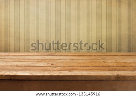 Vintage wooden deck table over retro wallpaper - stock photo