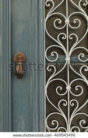 Vintage wooden door with knocker and spiral metal pattern background.