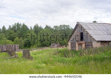 Vintage wooden houses on blossomin meadow. Verkhnee Zaozerye village, Novgorodskaya region, Russia.