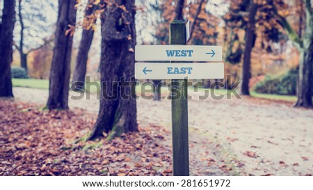 Vintage Wooden Signpost at the Quiet Park for West and East Directions Concept. - stock photo