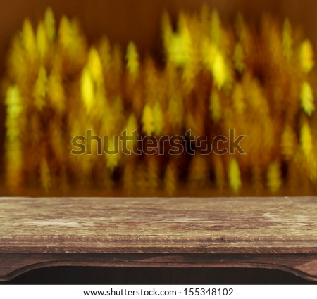 Vintage wooden table with christmas tree bokeh background - stock photo