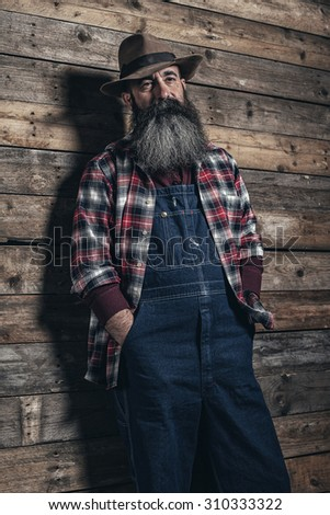 Vintage worker man with long gray beard in jeans dungarees. Standing in front of wooden wall. - stock photo