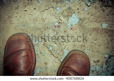 vintage worn-out boots on concrete floor, closeup - stock photo