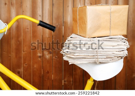Vintage yellow bicycle with newspaper and parcel, on wooden wall background - stock photo