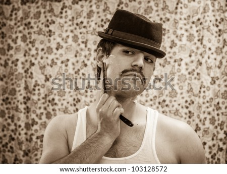 Vintage young white man in brown hat tank top mustache shaves stubble straight razor sepia tone