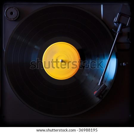 Vinyl disc playing in a slow photo. The main focus is in the disc. - stock photo