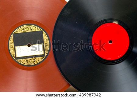 Vinyl record in front of a collection of albums, vintage process. Copy space for text.