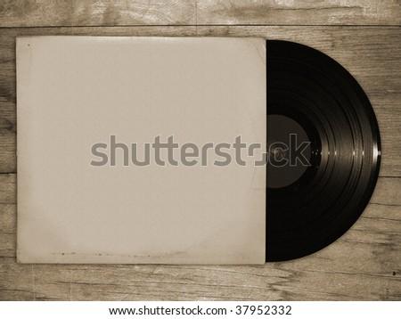 vinyl record on wooden table - stock photo