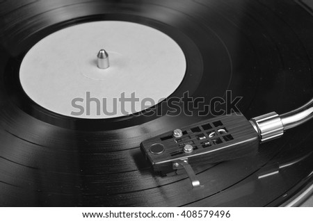 Vinyl record playing on a turntable in Monochrome. Music, dance and vintage theme - stock photo