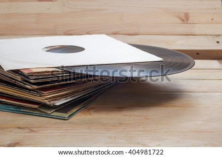 Vinyl record with copy space in front of a collection of albums (dummy titles), vintage process. Copy space. - stock photo