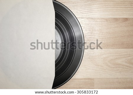 Vinyl record with cover on wooden table background