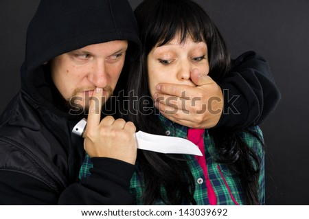 Violence, assault on a girl with a gun - stock photo