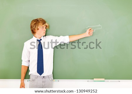 violent high school boy holding a gun drawn on chalkboard