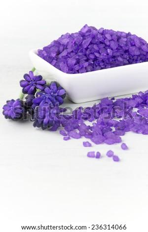 Violet bath salt in bowl on white wooden background. - stock photo
