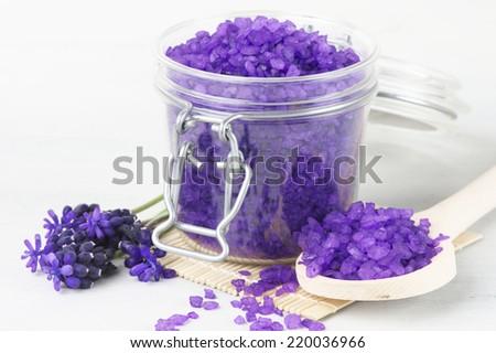 Violet bath salt in jar on white wooden background. - stock photo