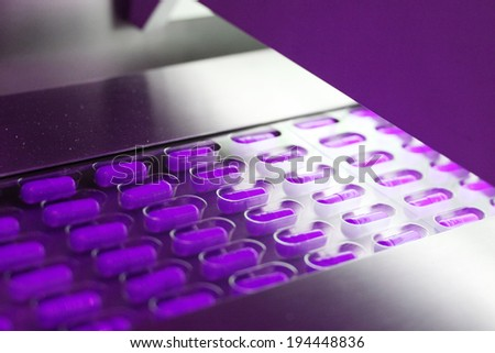 Violet capsules packed in tablet packing machine - stock photo