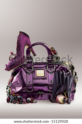 Violet elegance. Violet shoe on a purse with jewelry and gloves. - stock photo