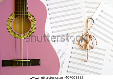 Violet guitar for children with treble clef on music sheets background - stock photo