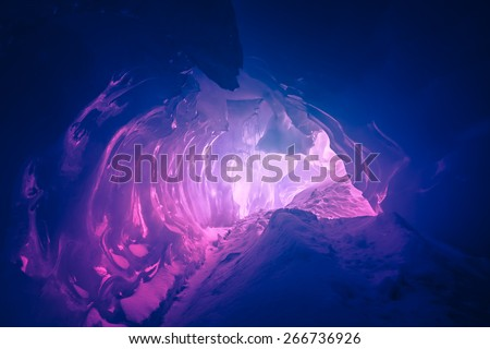 Violet ice cave covered with snow and flooded with light. Antarctica. Vernadsky Research Base.