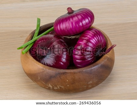 Violet onion in the basket with green - stock photo