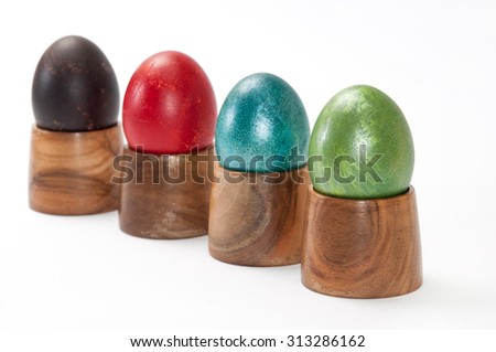 Violet, red, blue and green easter eggs in wooden holder.