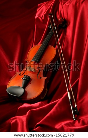 Violin and bow on red silk, music background - stock photo