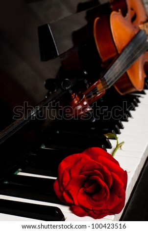 Violin and piano closeup with red rose for concert advertisement with copy-space - stock photo