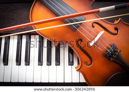 Violin and piano keyboard. Music background. Top view. Dark vignette. - stock photo