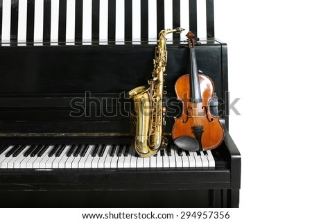 Violin and saxophone on piano background - stock photo