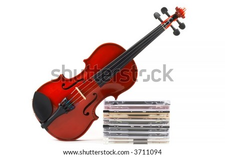 Violin leaning on stack of compact discs on white background, top angle view, horizontal orientation. Depicts a career in classical music. Commercialization of classical music. - stock photo