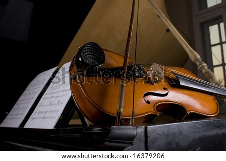 Violin on grand piano with notes sheets - stock photo
