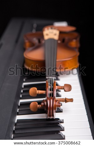 Violin on the piano on a black background - stock photo