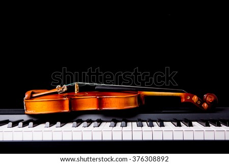 Violin on the piano on black background - stock photo
