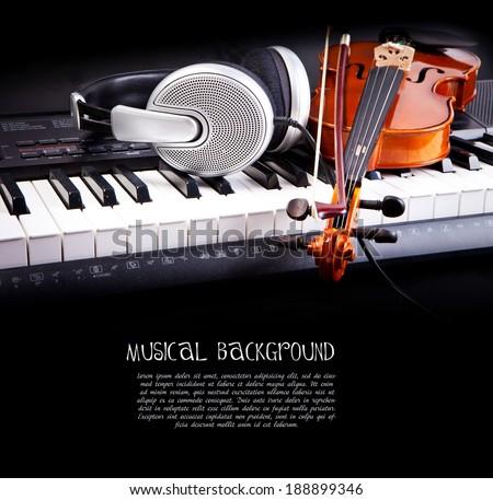 Violin, piano keys and headphones on black - stock photo