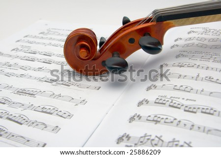 Violin scroll resting on a sheet music - stock photo