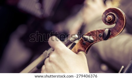 Violinist hand and his music instrument. Violin and bow in the hands of the musician on a blurred background. Violin closeup at soft focus, toning of instagram  filter. - stock photo